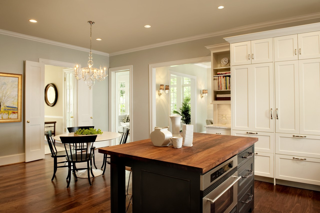 View of kitchen designed by Nadia Subaran. Designed cabinetry, ceiling, countertop, cuisine classique, dining room, floor, flooring, furniture, hardwood, home, interior design, kitchen, room, table, wood flooring, orange