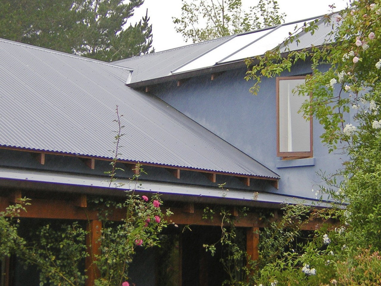 This large home efficiently uses solar energy thanks facade, home, house, outdoor structure, real estate, roof, tree, wood, gray, brown