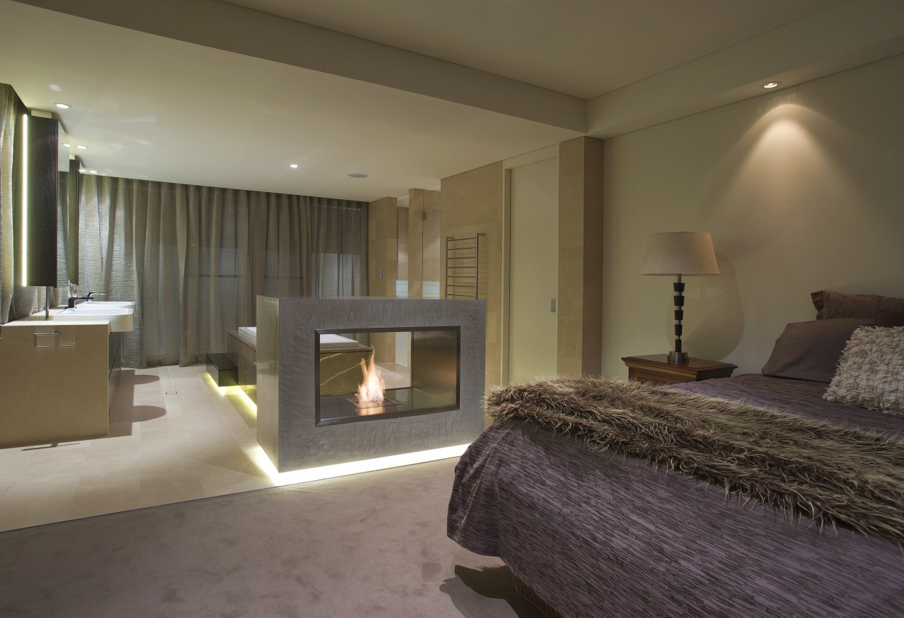 Bedroom with purple bedspread and fireplace. bed frame, bedroom, ceiling, floor, hearth, interior design, property, real estate, room, suite, wall, brown