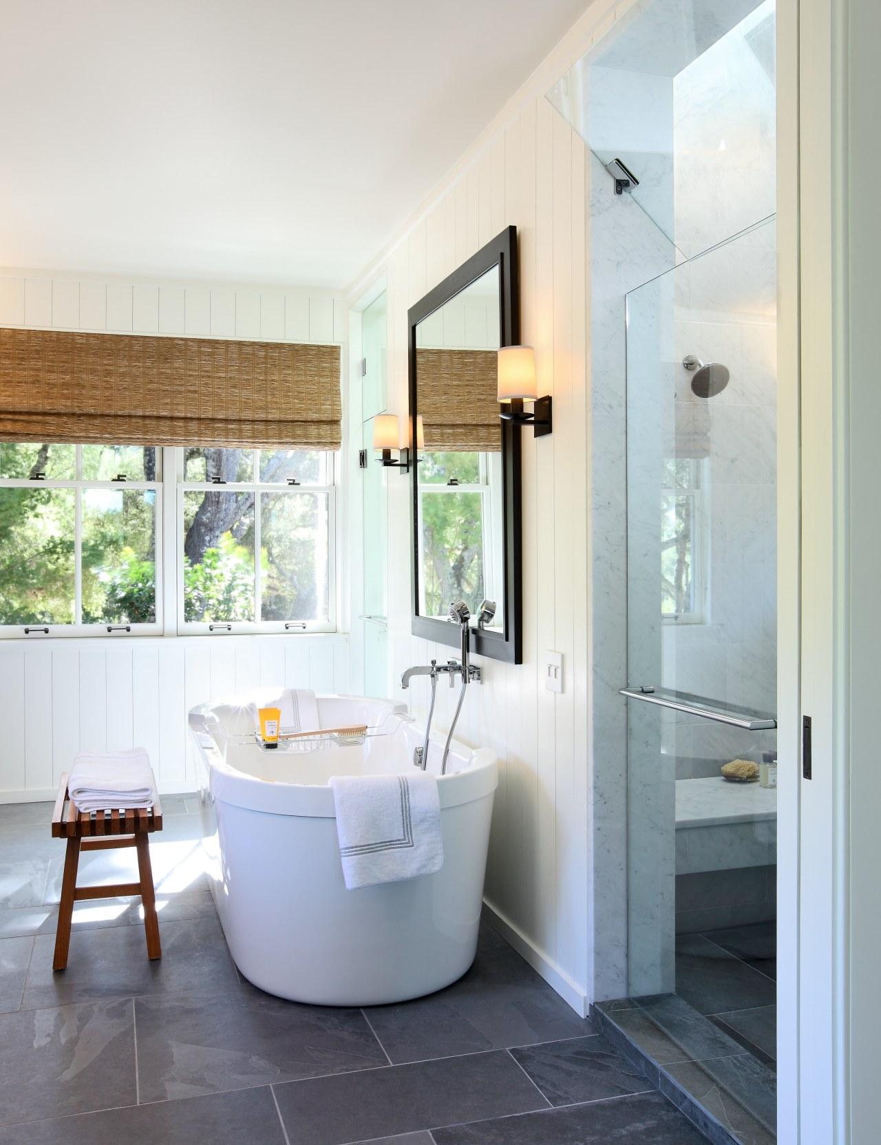 Bathroom with grey tiled flooring and white tub. bathroom, floor, home, interior design, plumbing fixture, real estate, room, window, white