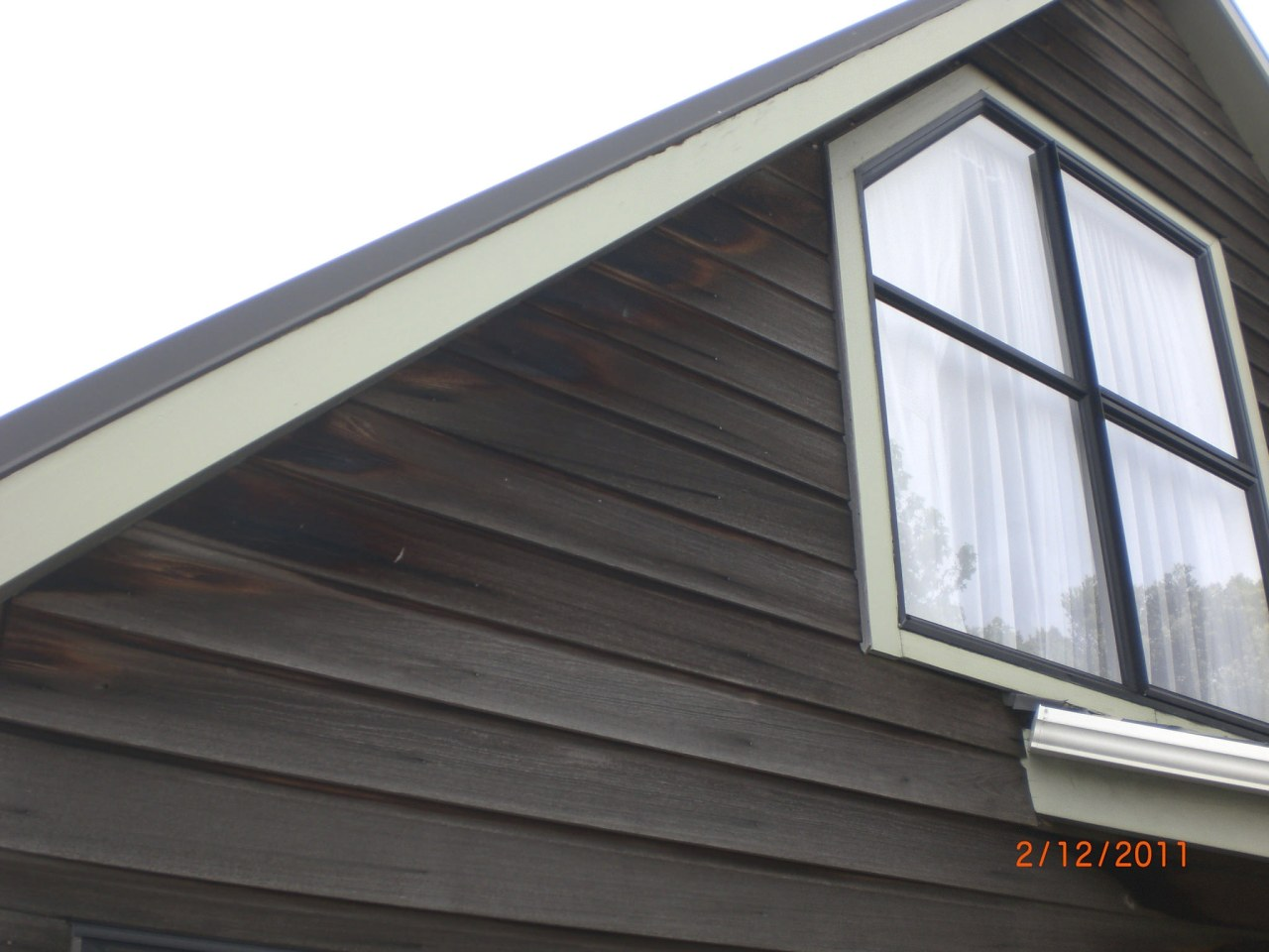 Resene Waterborne Woodsman was used on this daylighting, facade, home, roof, siding, window, black, white