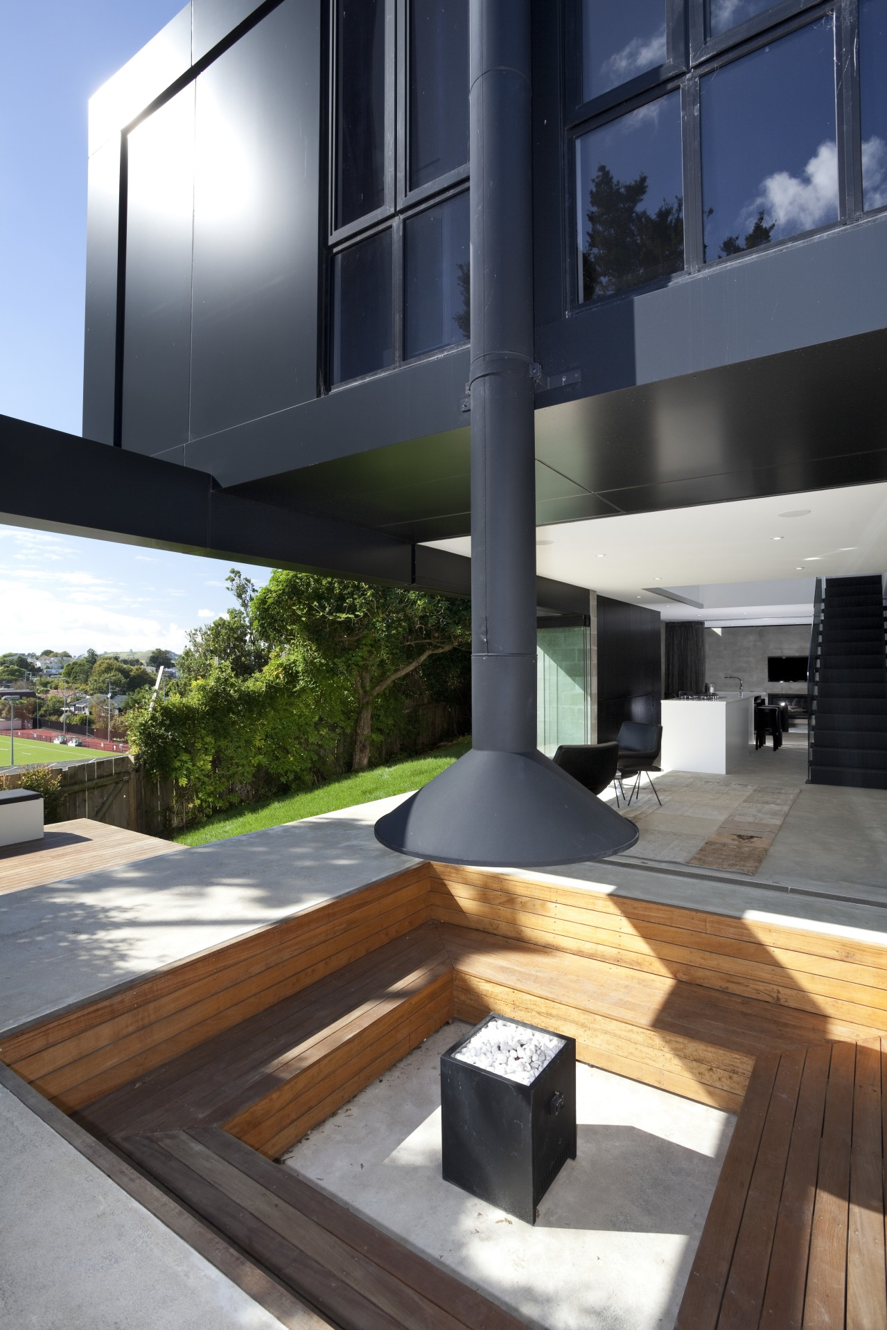 Fire pit seating area outside. Timber area, beneath architecture, condominium, daylighting, house, interior design, black