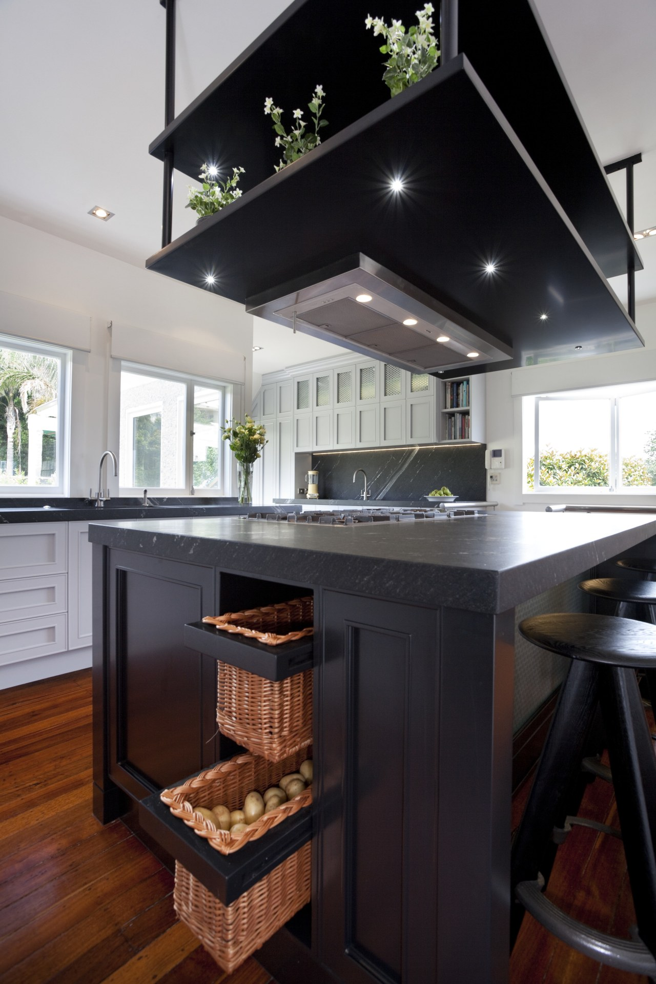 Dark stained central island, powerpack above on tiered countertop, interior design, kitchen, black