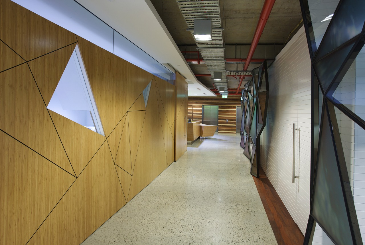 Hallway with triange cutout design on walls. architecture, ceiling, daylighting, floor, wood, brown, gray