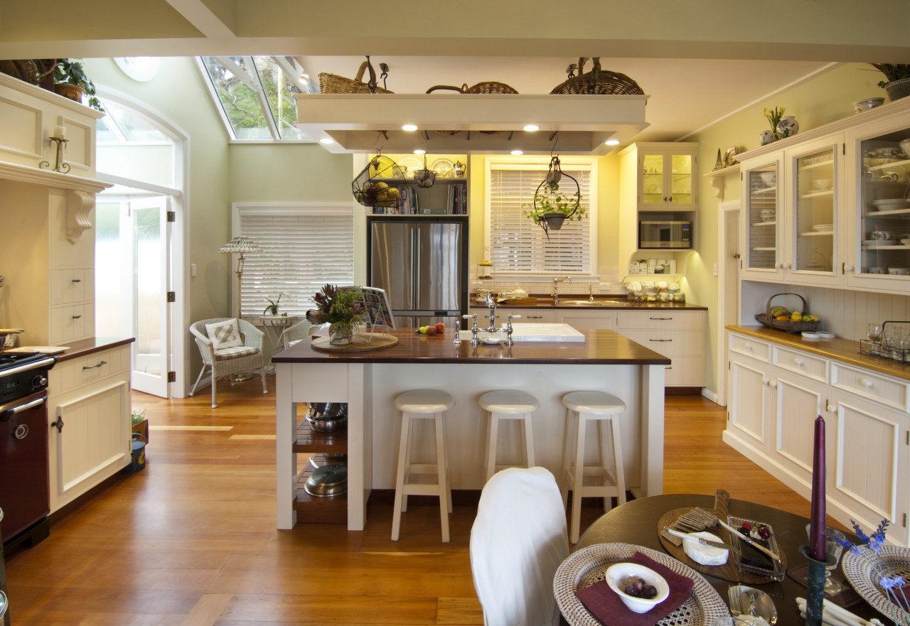 central island features seating and white stoold. rangehood cabinetry, ceiling, countertop, cuisine classique, hardwood, home, interior design, kitchen, living room, room, brown, orange