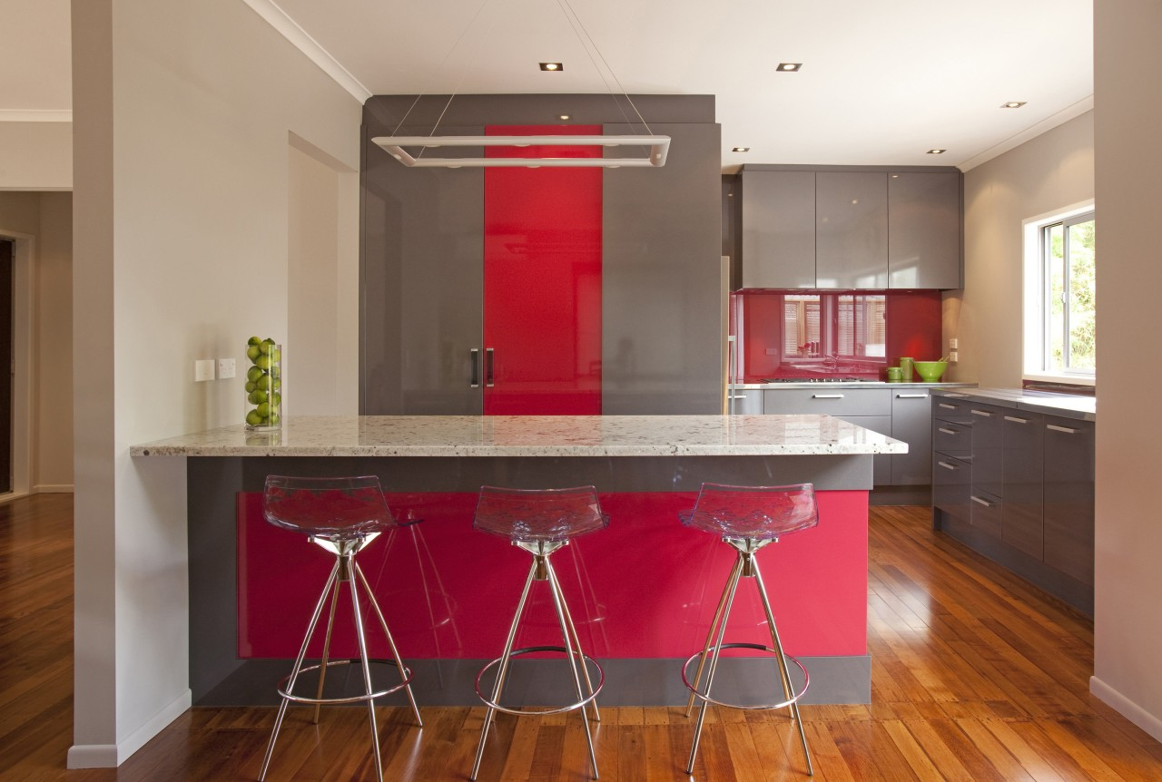 Streamlined grey kitchen with red accents. Peniinsula with cabinetry, countertop, floor, flooring, hardwood, interior design, kitchen, property, real estate, room, table, brown