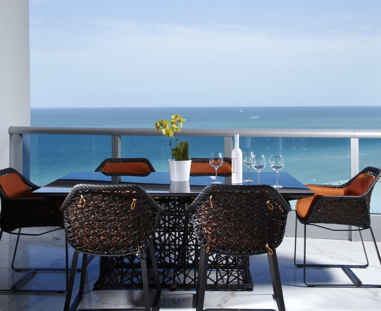 A pop of orange enlivens the black lattice chair, furniture, outdoor furniture, sea, sunlounger, table, vacation, teal