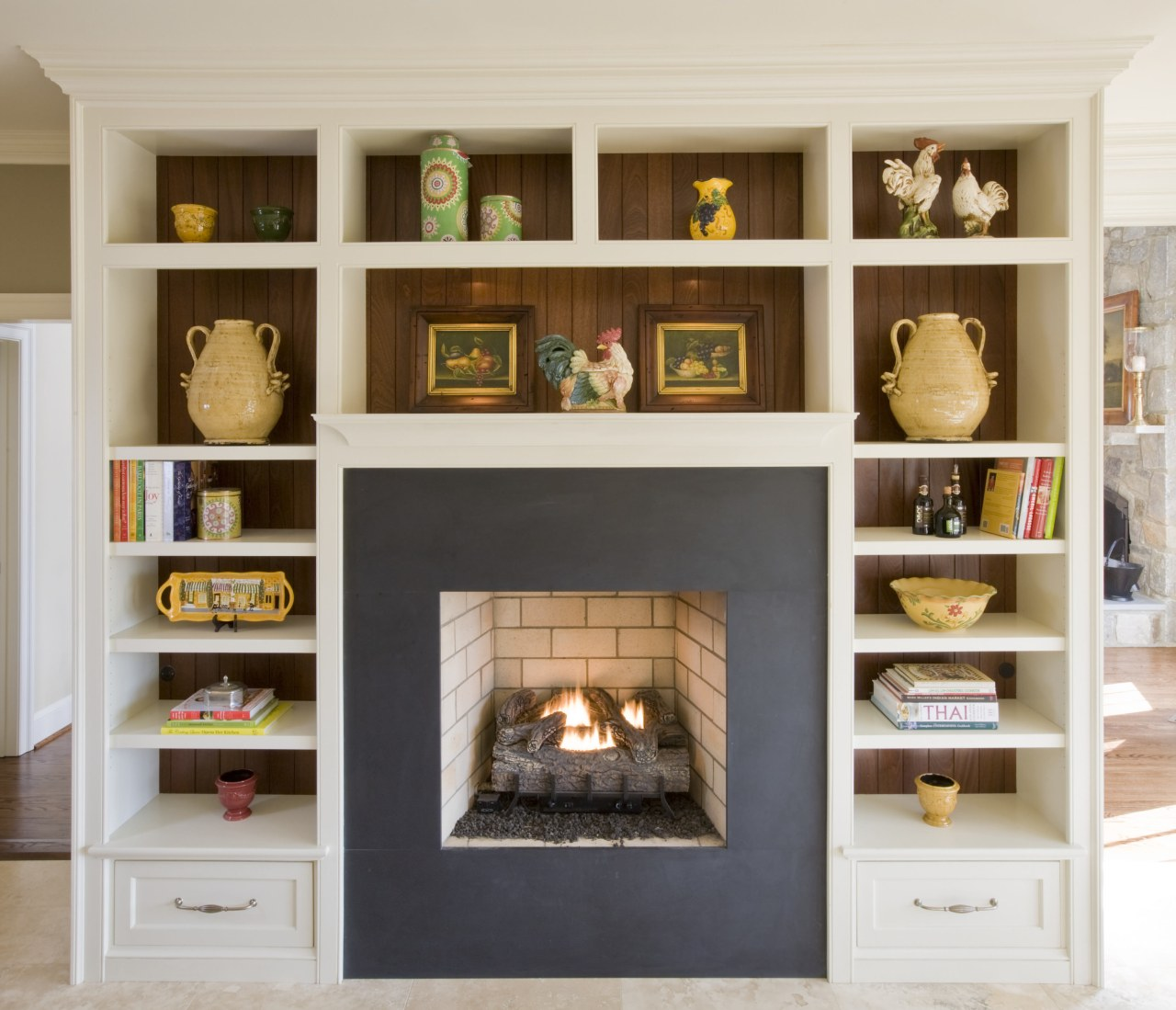 For centuries, the hearth has been the center bookcase, cabinetry, fireplace, furniture, hearth, home, living room, shelf, shelving, white