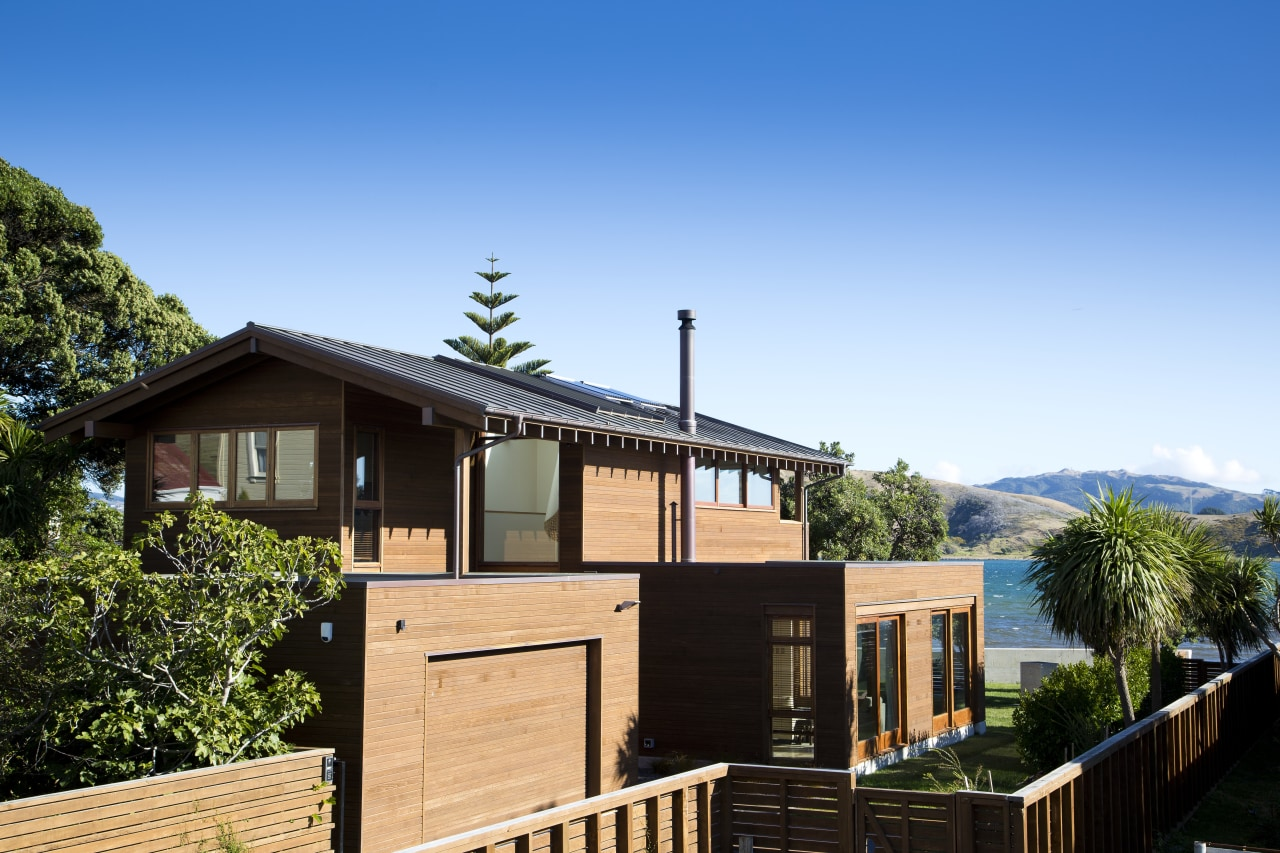 The sides and street facade of this contemporary cottage, estate, facade, home, house, outdoor structure, plant, property, real estate, residential area, roof, sky, tree, villa, teal