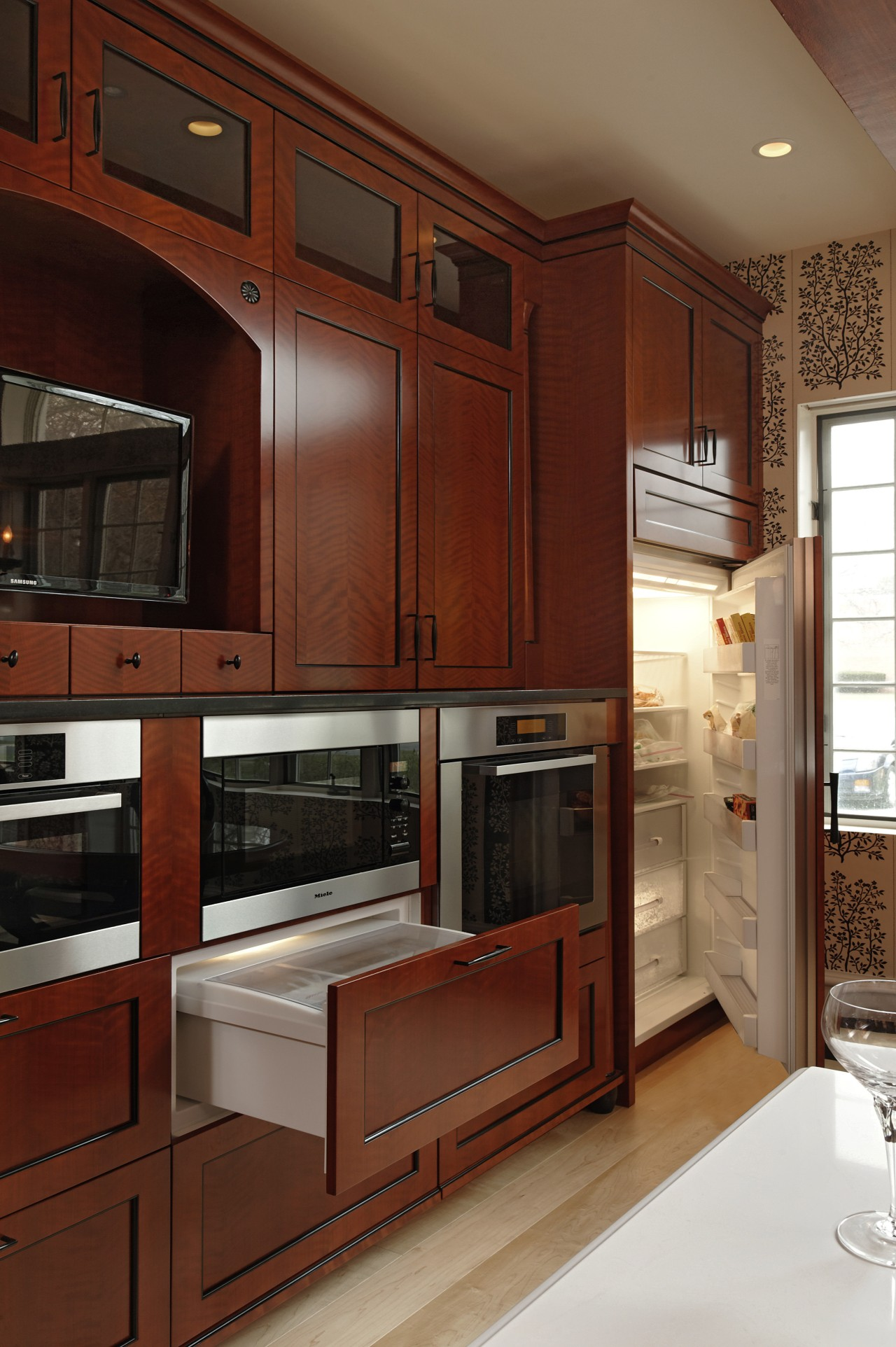 A bank of Rosewood kitchen cabinetry, containing integrated cabinetry, countertop, cuisine classique, furniture, interior design, kitchen, room, under cabinet lighting, wood, brown, red