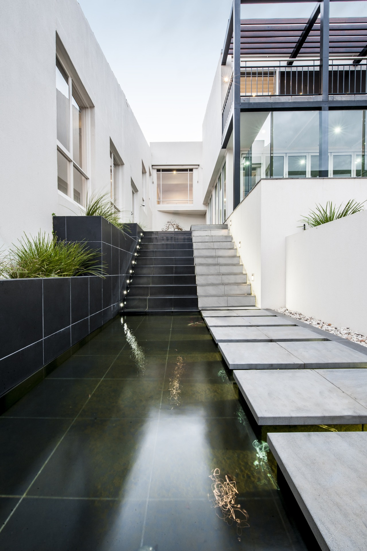 A water feature, lined with dark tiles, provides apartment, architecture, building, condominium, daylighting, estate, facade, home, house, property, real estate, reflection, residential area, white