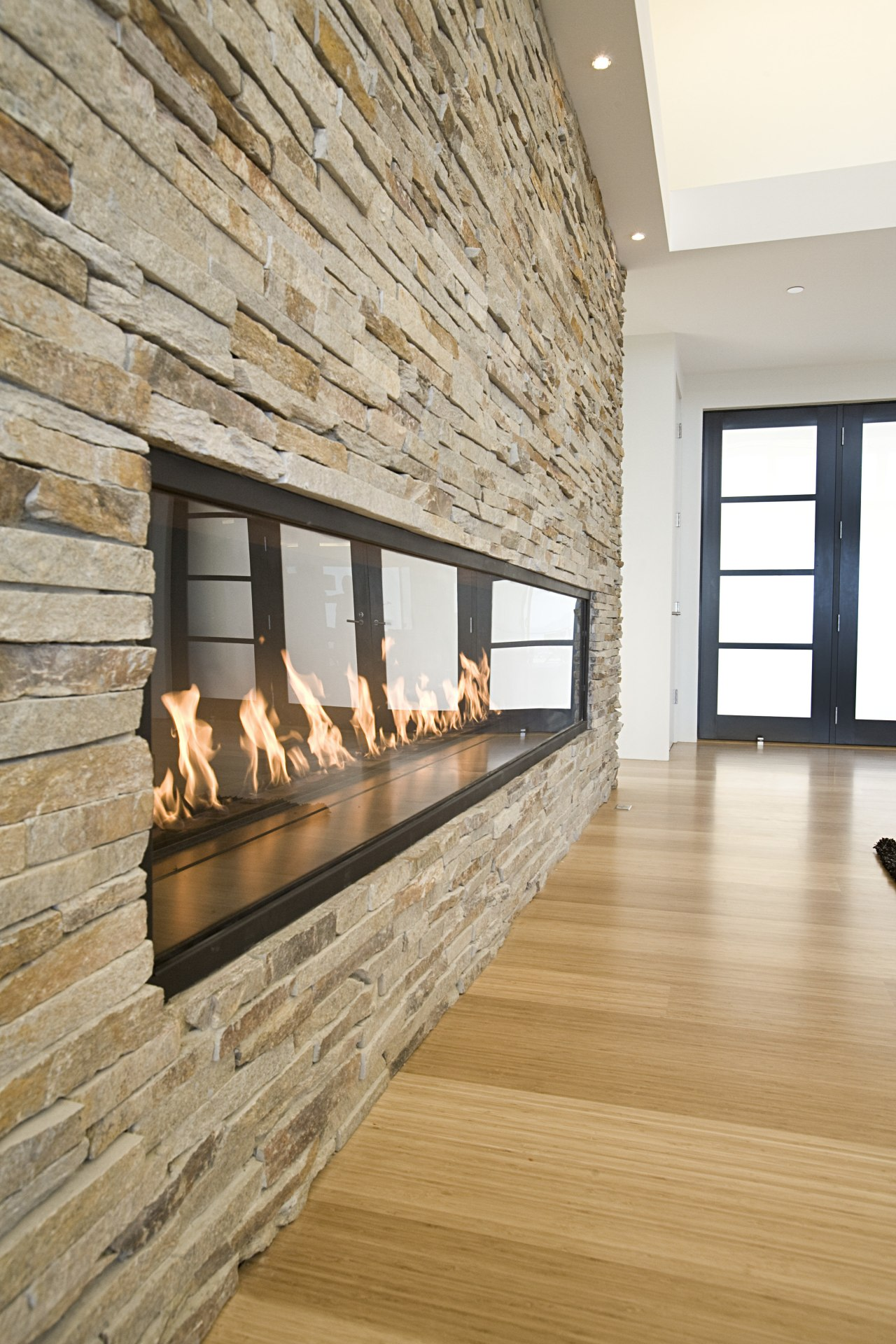 This modern home features a soaring natural stone fireplace, floor, flooring, hardwood, hearth, interior design, laminate flooring, living room, wood, wood flooring, gray, orange