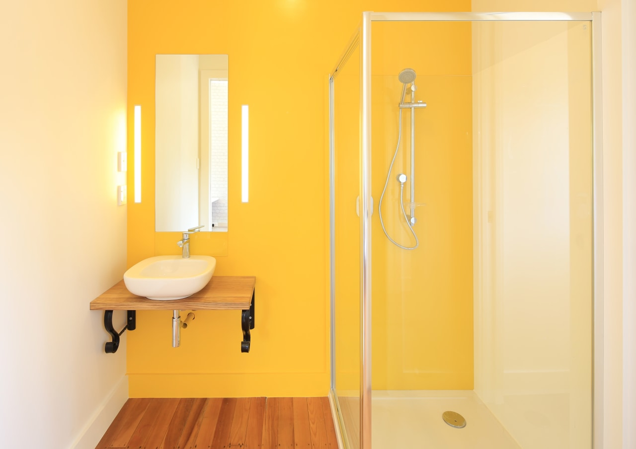 Oversized cavity sliders and lively yellow wall paint bathroom, floor, interior design, plumbing fixture, product design, room, wall, yellow, orange