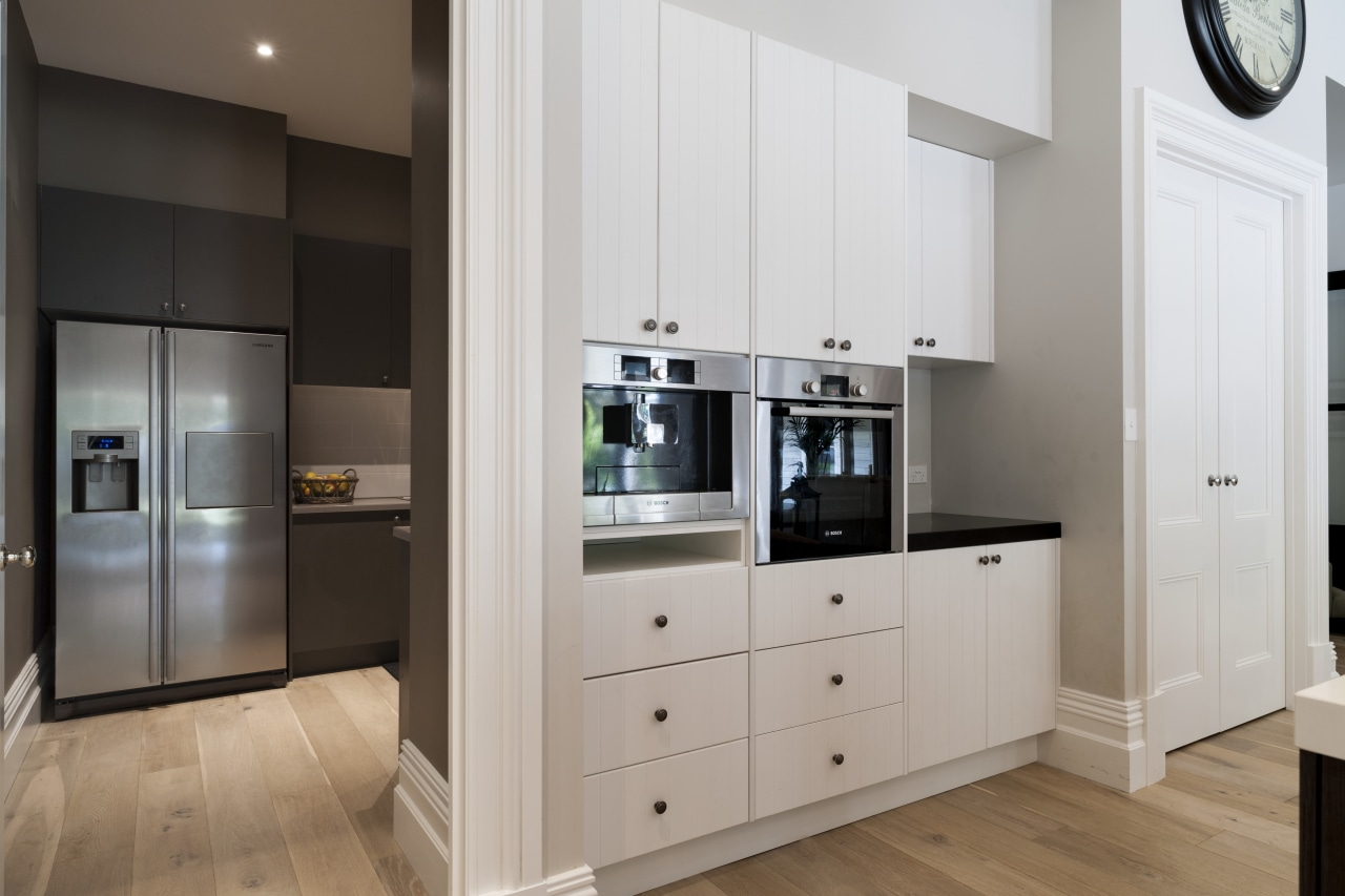 The L-shaped butlers pantry is contemporary, with modern cabinetry, countertop, floor, home appliance, interior design, kitchen, room, gray
