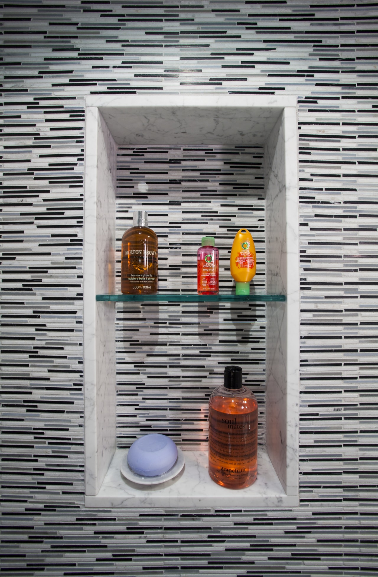 A recessed soap and shampoo niche maximizes usable glass, wall, gray