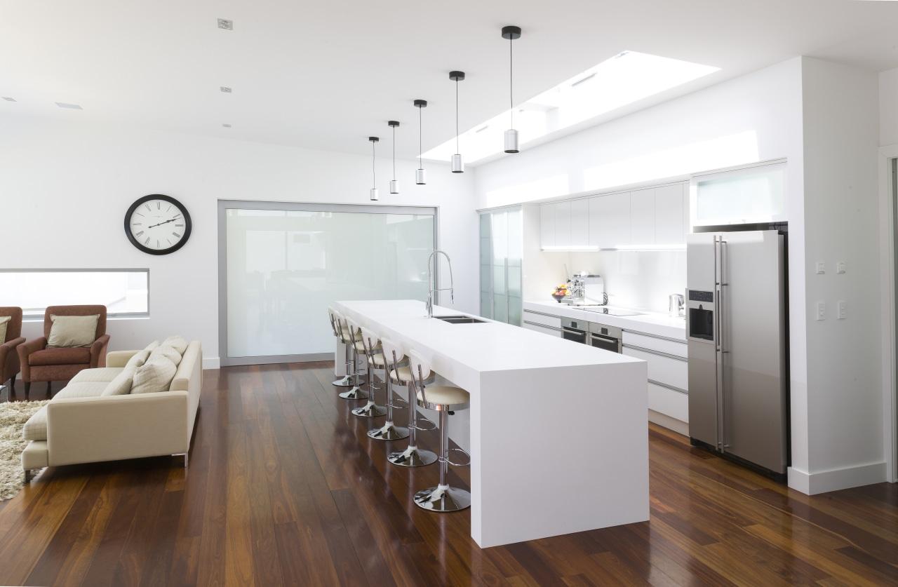 Contemporary white kitchen with large island. Internal sliding floor, flooring, interior design, interior designer, kitchen, living room, real estate, wood flooring, white