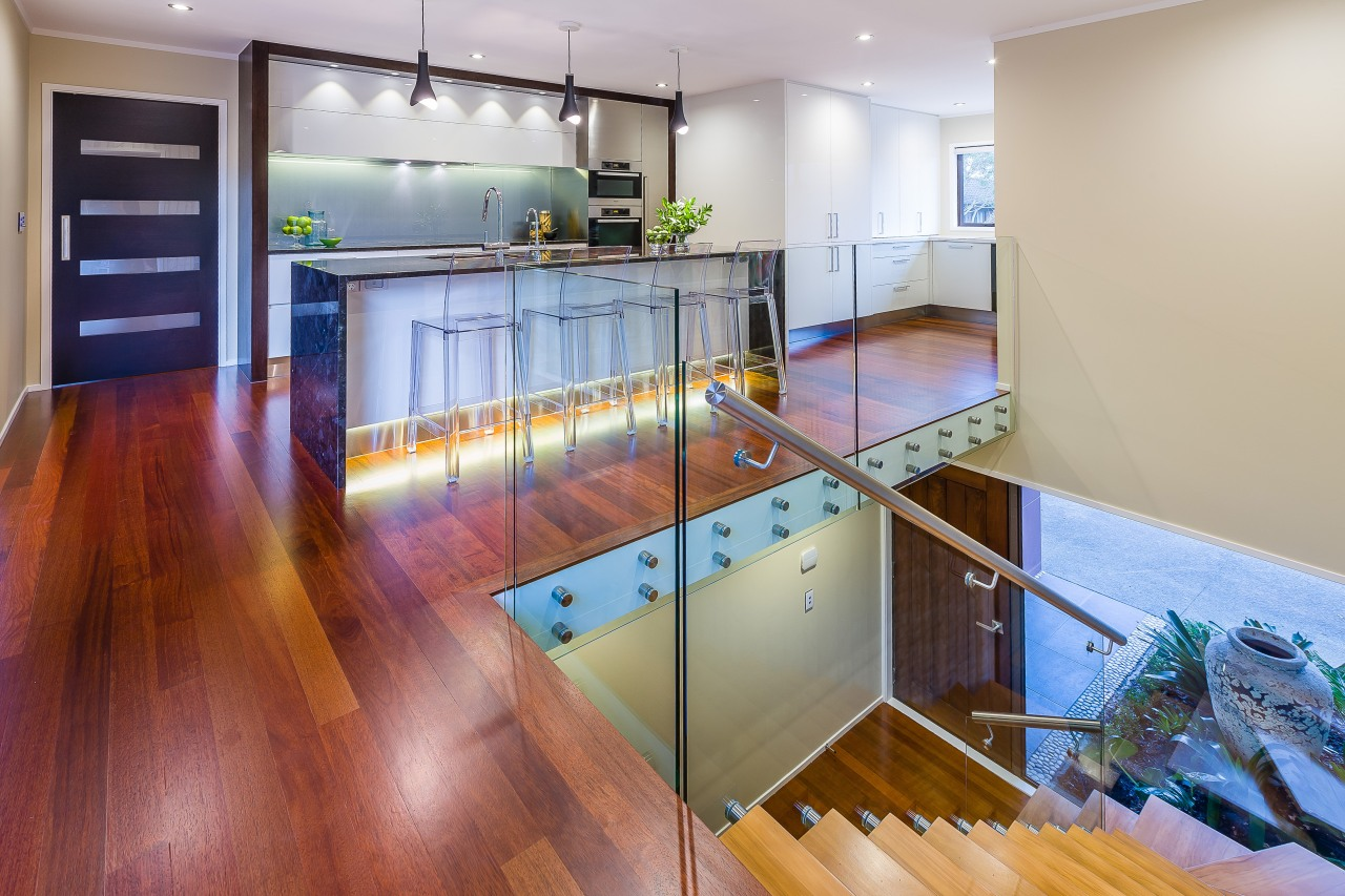 Glass balustrading enhances the sense of space and countertop, floor, flooring, hardwood, interior design, kitchen, laminate flooring, loft, real estate, room, wood, wood flooring, gray