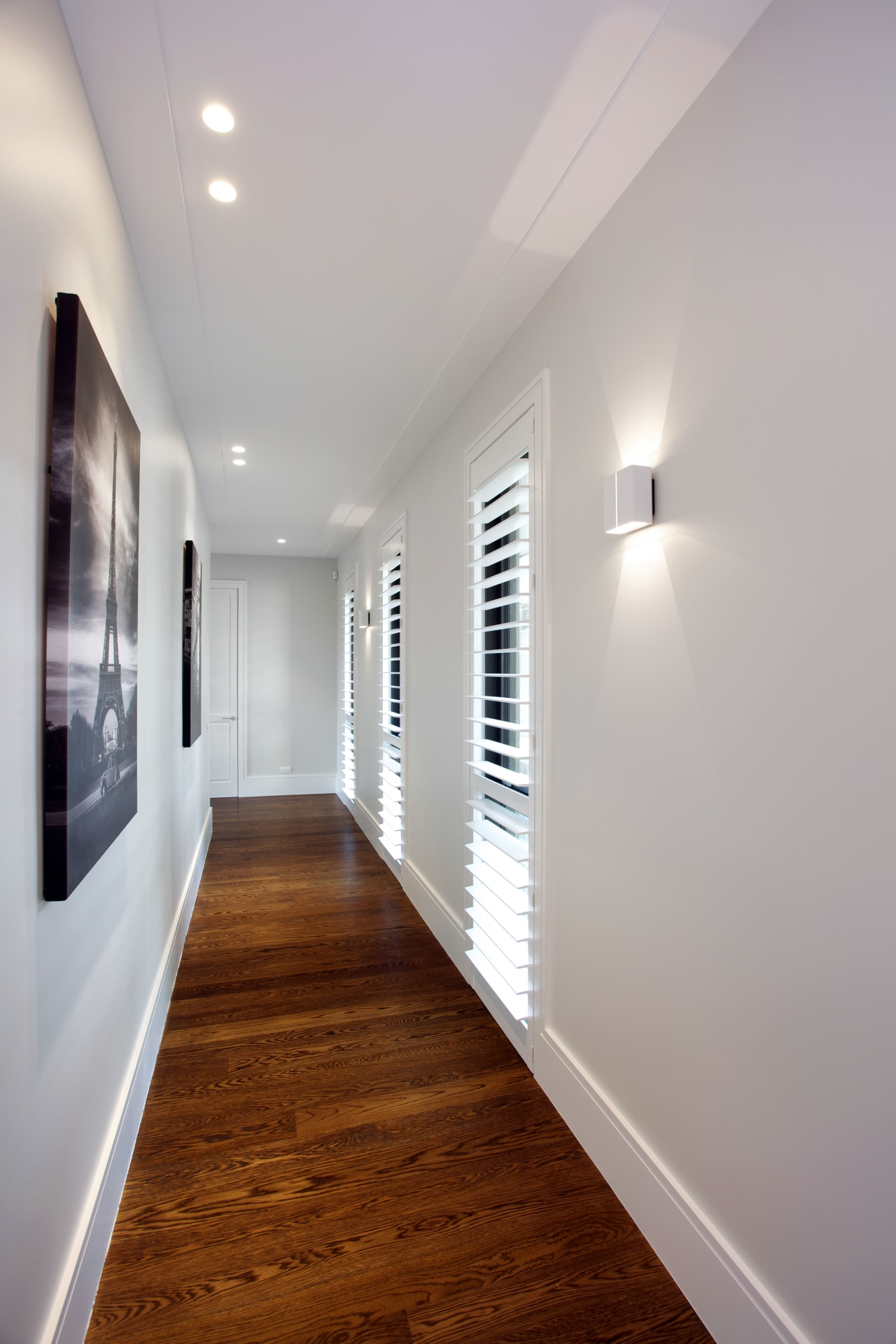 White walls in this circulation area provide a apartment, architecture, ceiling, daylighting, floor, flooring, hardwood, home, house, interior design, lighting, real estate, room, wood, wood flooring, gray