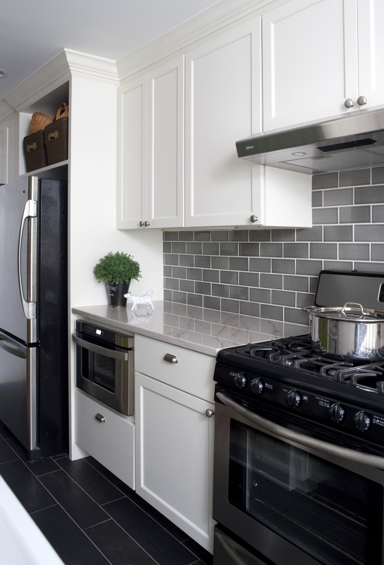 A small work triangle provides a highly efficient cabinetry, countertop, cuisine classique, gas stove, home, home appliance, interior design, kitchen, kitchen appliance, kitchen stove, major appliance, microwave oven, refrigerator, room, white, black