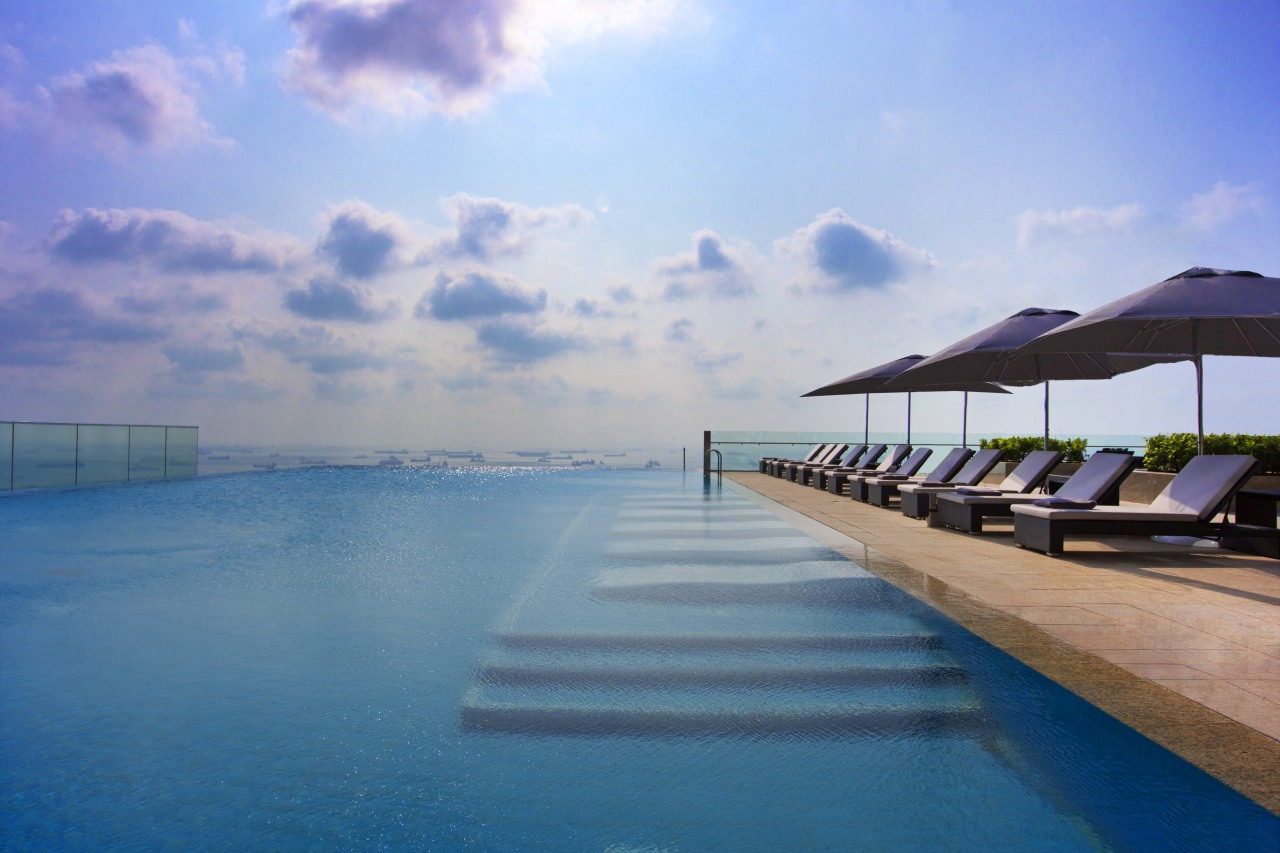With its infinity edge, the rooftop pool appears calm, caribbean, cloud, coastal and oceanic landforms, estate, evening, horizon, lagoon, leisure, ocean, real estate, resort, resort town, sea, sky, sunlight, swimming pool, tropics, vacation, water, teal, gray