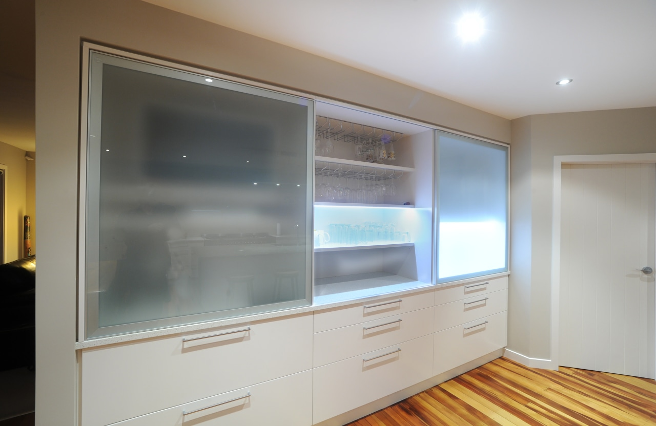 This kitchen includes opaque glass sliders that conceal cabinetry, furniture, interior design, room, wall, window, gray
