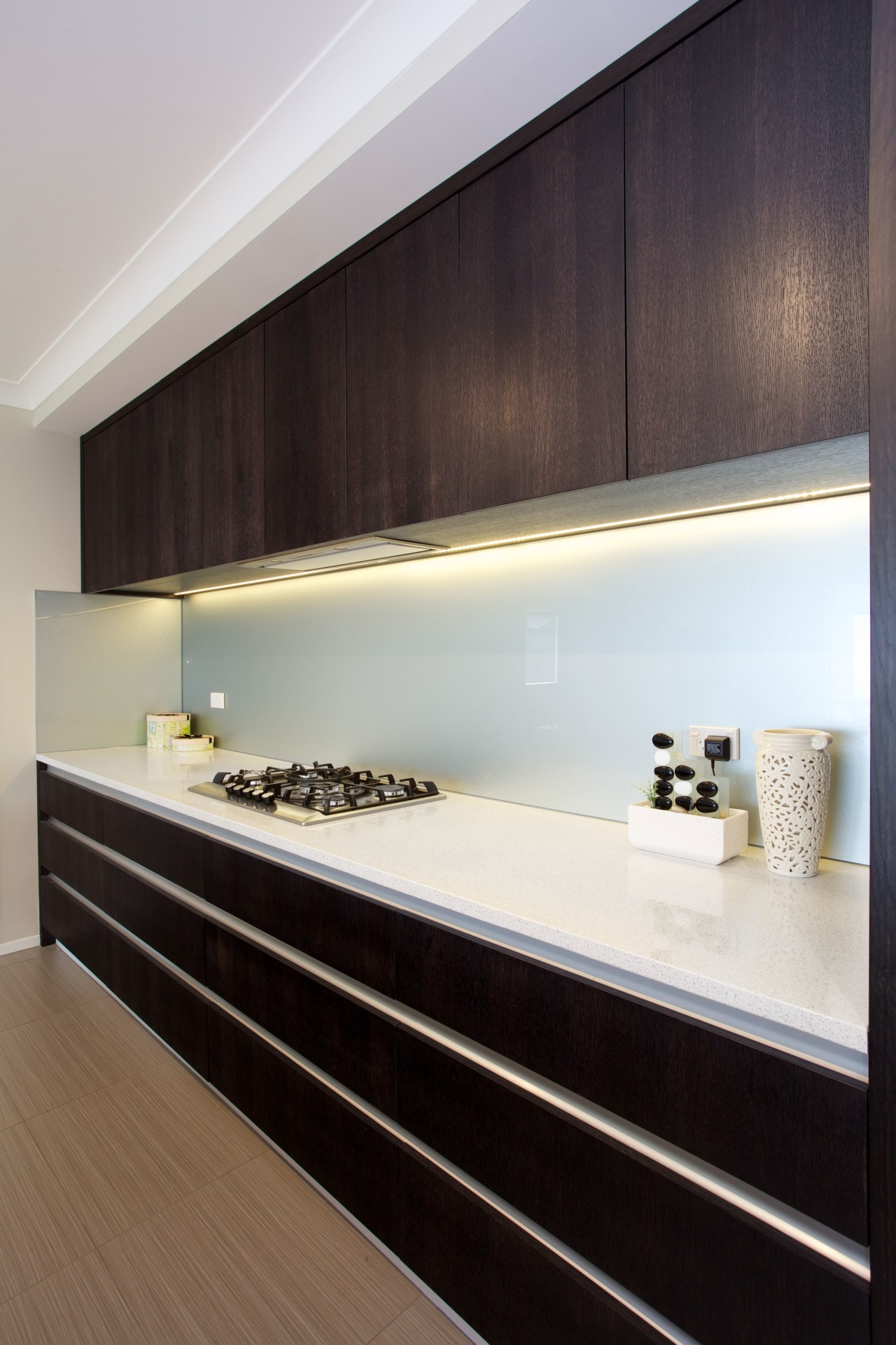 Dark-stained timber veneer cabinets line the rear wall architecture, floor, flooring, interior design, kitchen, room, wall, wood, gray, black