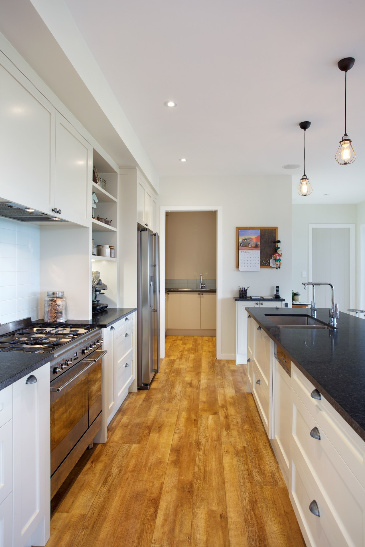 This galley kitchen features Shaker-style cabinets and honed cabinetry, countertop, cuisine classique, floor, flooring, hardwood, interior design, kitchen, laminate flooring, real estate, room, wood, wood flooring, gray