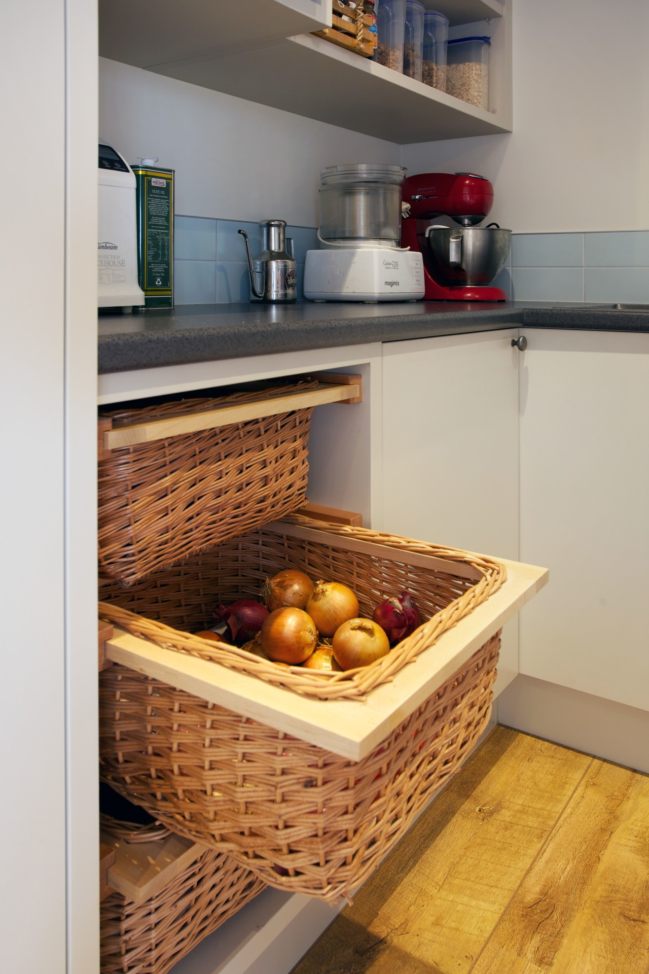There are pull-out wicker baskets for storing vegetables countertop, flooring, kitchen, gray