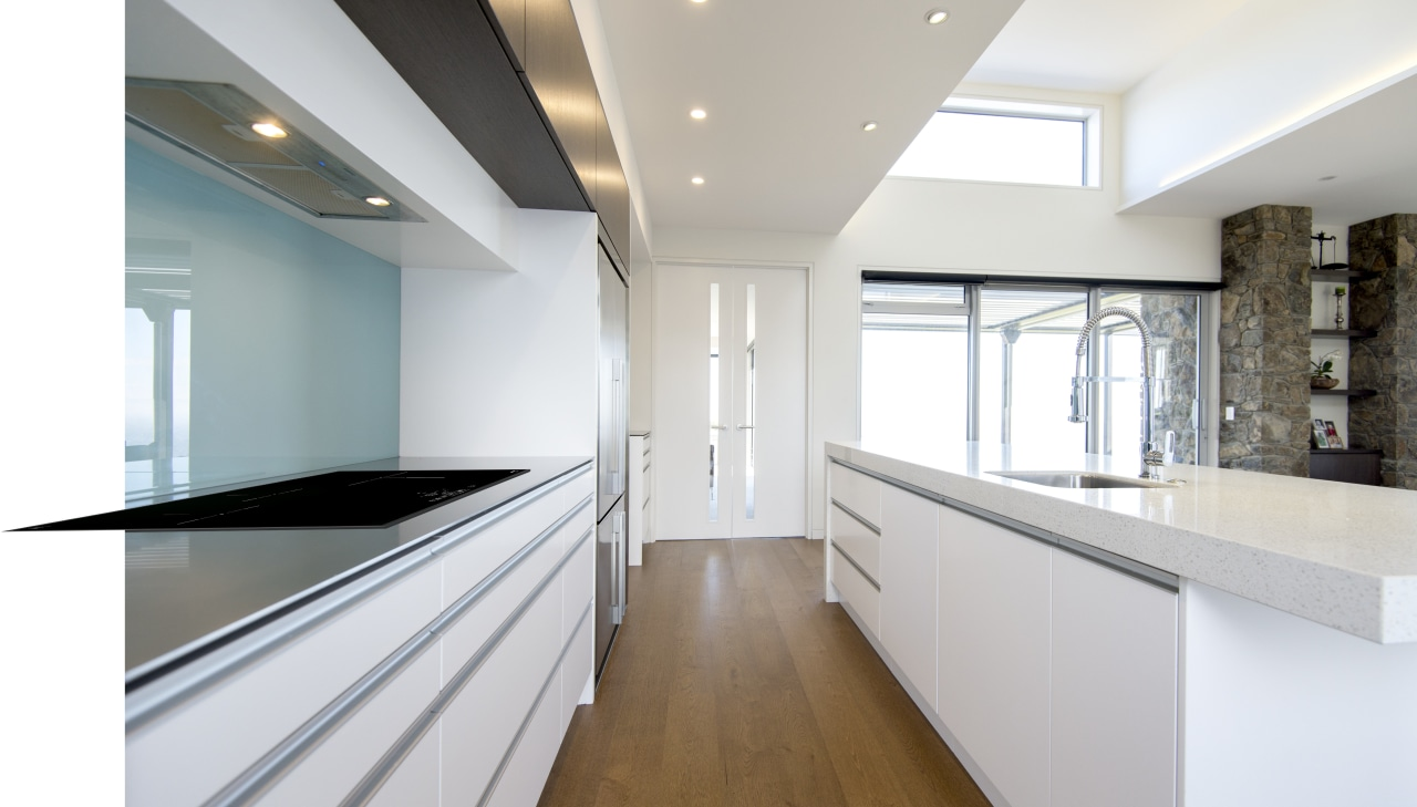 This galley-style kitchen showcases a full suite of ceiling, countertop, daylighting, floor, home, house, interior design, kitchen, property, real estate, room, white