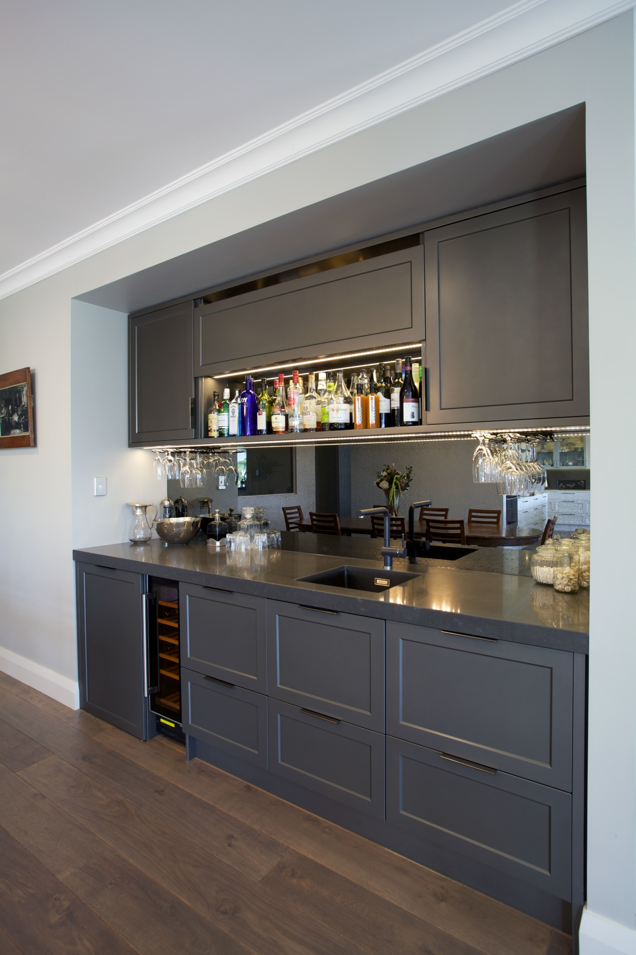 A mirror splashback and uniform grey tones give cabinetry, countertop, cuisine classique, home appliance, interior design, kitchen, room, gray, black