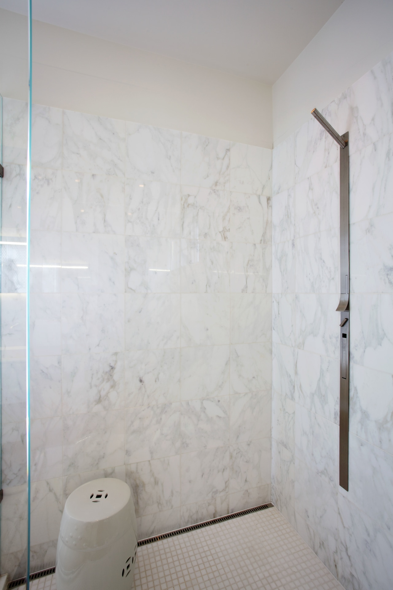 This shower stall has a Carrara marble lining bathroom, ceiling, floor, flooring, interior design, plaster, plumbing fixture, room, tile, wall, gray