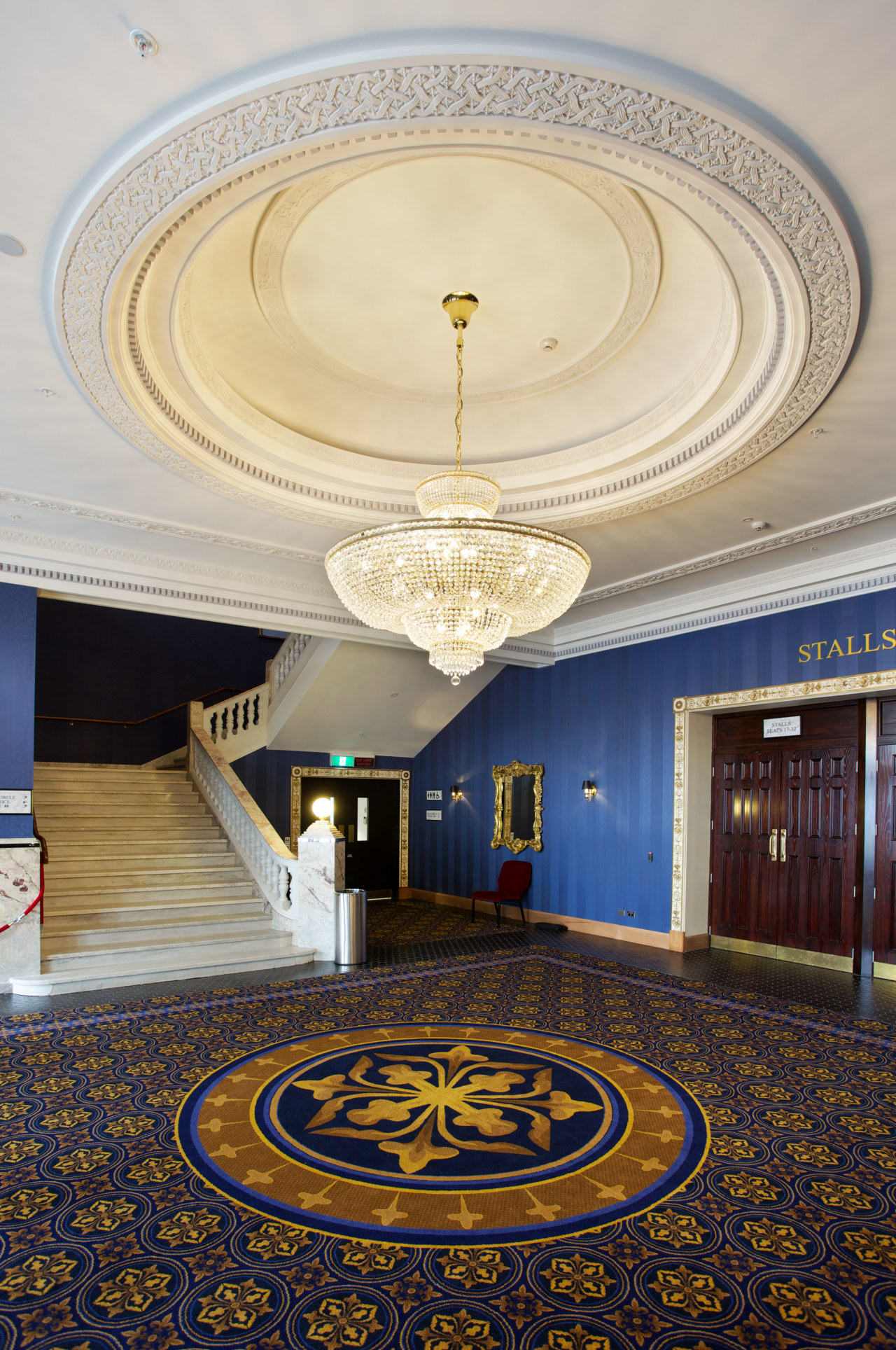:Custom chandeliers at the Isaac Theatre Royal were architecture, ceiling, column, daylighting, estate, floor, flooring, interior design, lobby, structure, symmetry, wall, gray
