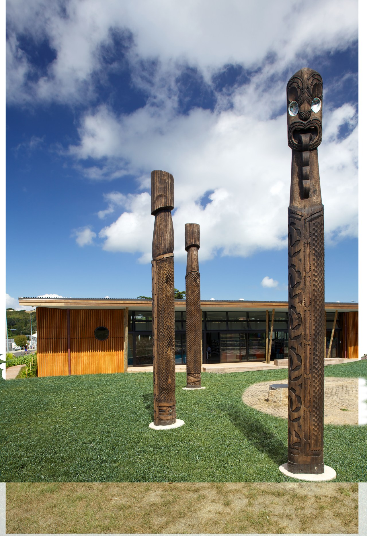 Carved timber battens wrap around the exterior of cloud, column, grass, sky