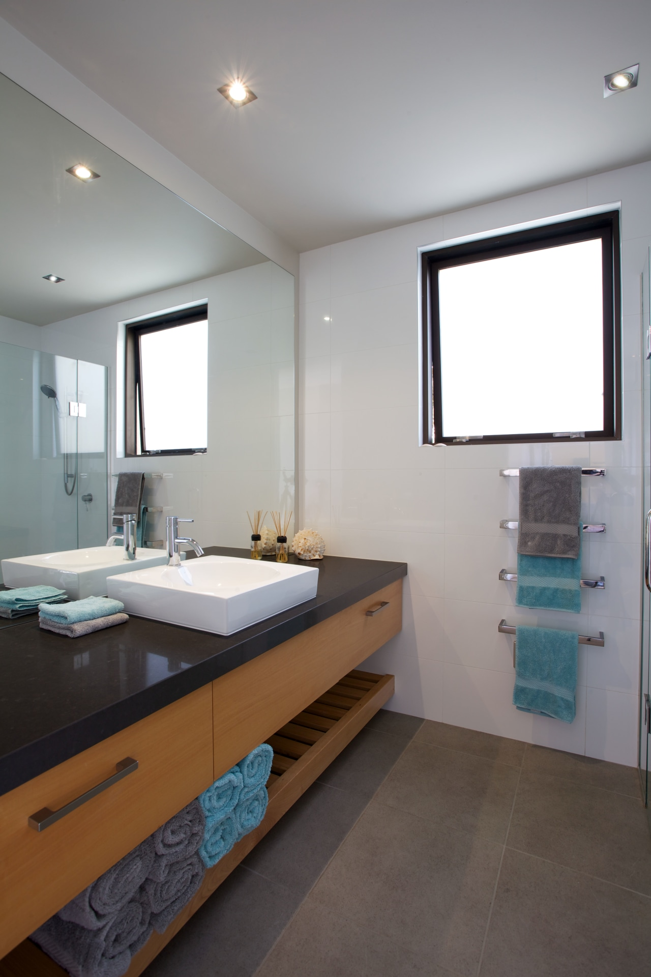 A large bathroom mirror creates the illusion of architecture, bathroom, countertop, floor, home, interior design, real estate, room, sink, gray