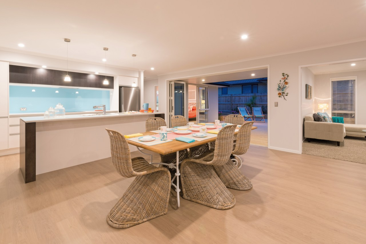 A galley-style kitchen is the social hub of apartment, floor, flooring, hardwood, interior design, living room, property, real estate, room, orange