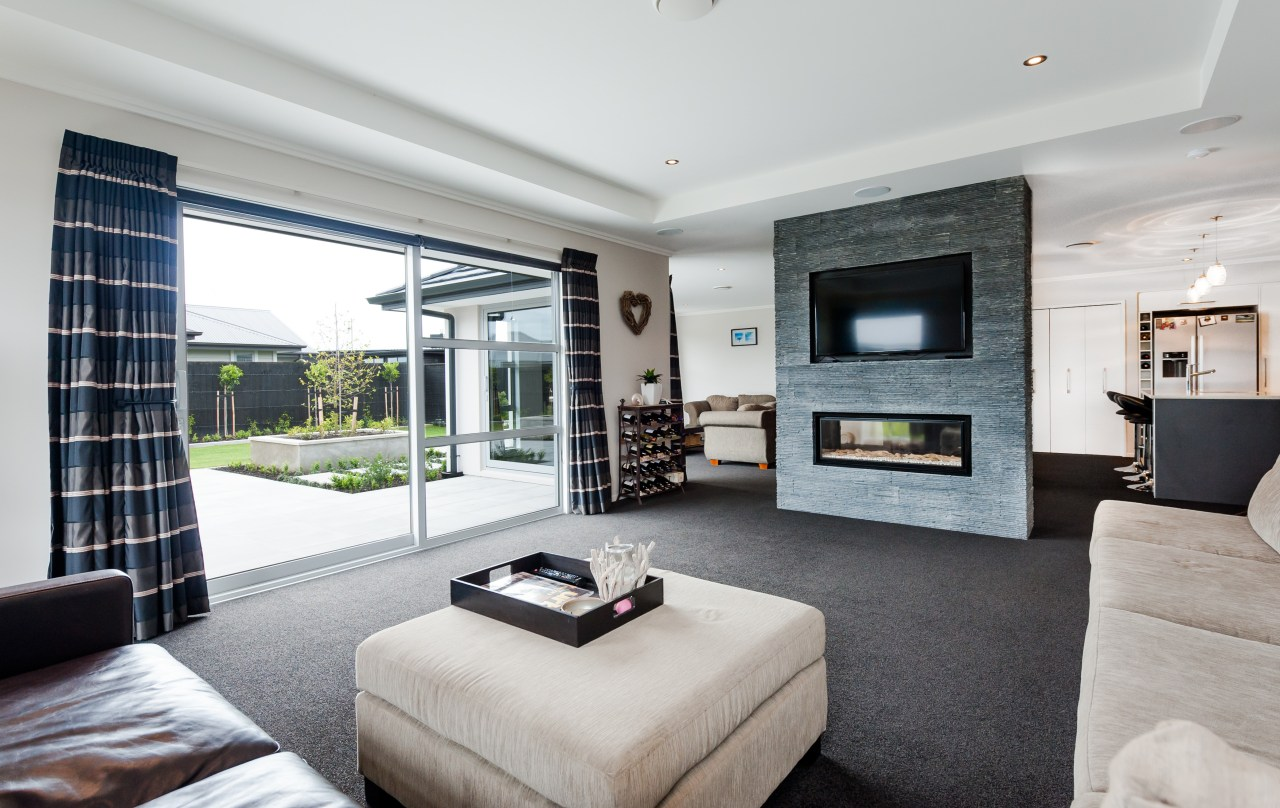 A two-sided fireplace features in this house by estate, home, interior design, living room, property, real estate, gray