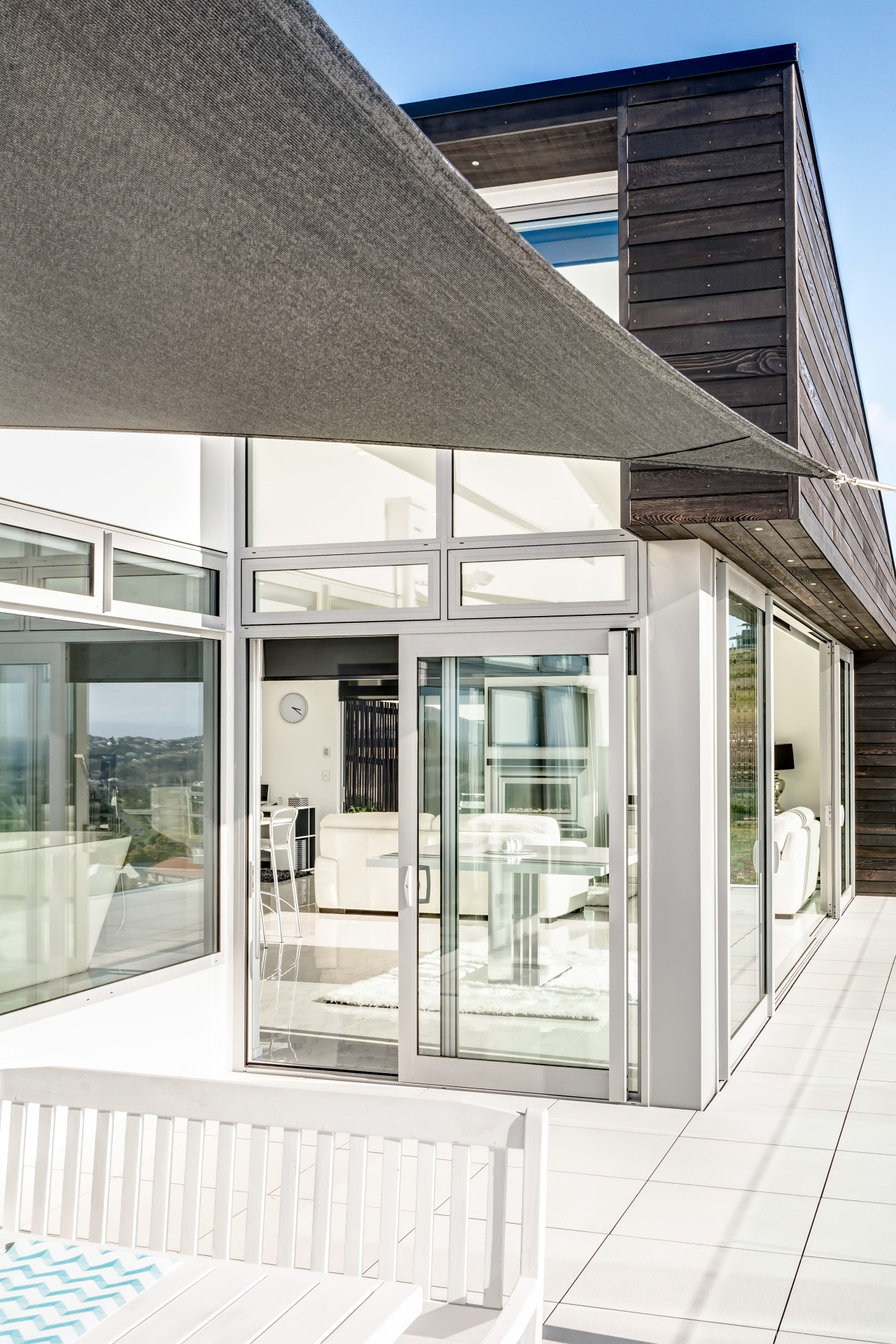 A sail shade shelters the outdoor dining area architecture, building, daylighting, facade, glass, house, window, white