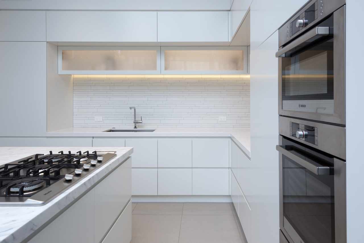 Translucent glass upper cabinetry adds to the sense cabinetry, countertop, interior design, kitchen, kitchen stove, product design, sink, gray