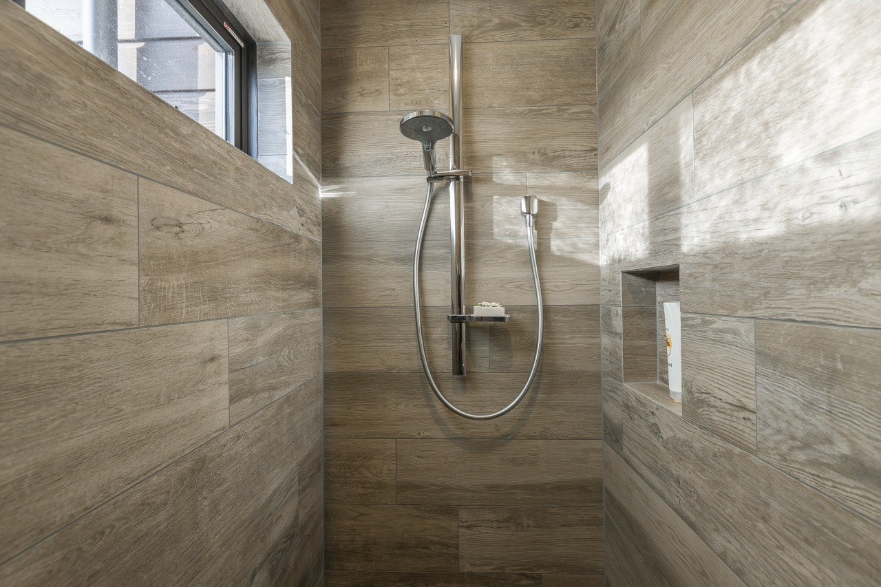 Built-in niches provide shelving for soaps and shampoos architecture, bathroom, daylighting, floor, plumbing fixture, tile, wall, wood, brown, gray