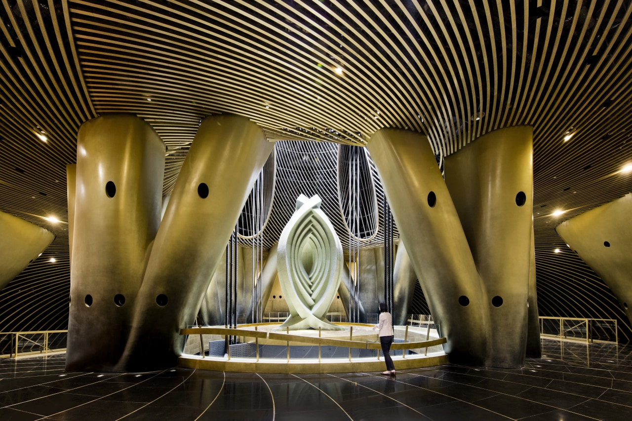 An artistic installation sits above the Shanghai Towers architecture, ceiling, light, lighting, night, performing arts center, structure, symmetry, black, brown