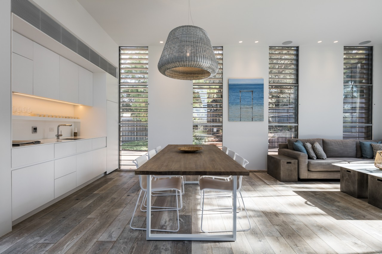 Room-height shutters and corresponding windows admit ample natural architecture, floor, furniture, interior design, living room, table, gray