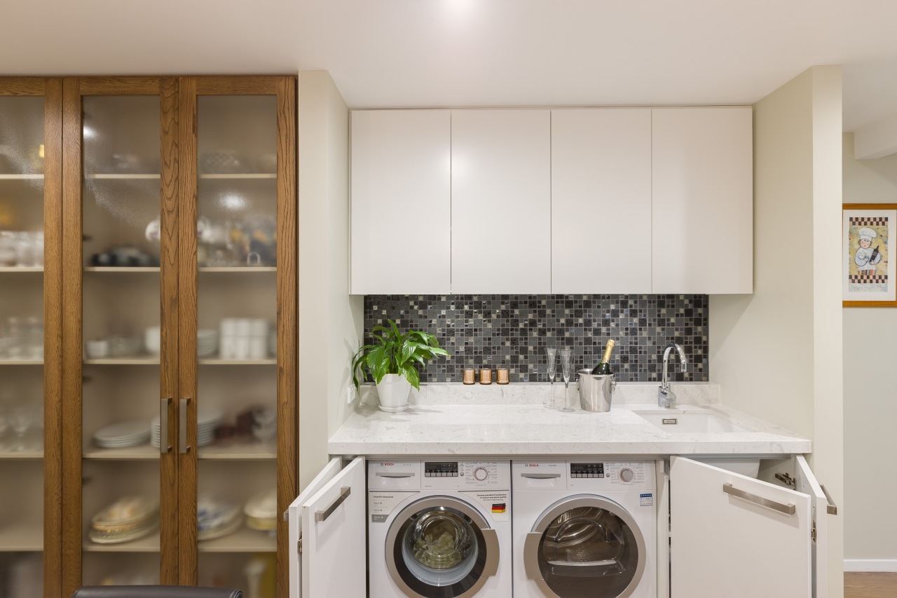 Blade walls were introduced to define the laundry cabinetry, countertop, cuisine classique, home appliance, kitchen, laundry, laundry room, major appliance, room, gray, brown