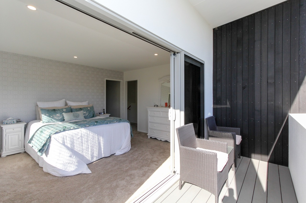 Stacker doors provide a seamless indoor-outdoor connection in bedroom, ceiling, floor, home, interior design, property, real estate, room, suite, wall, gray