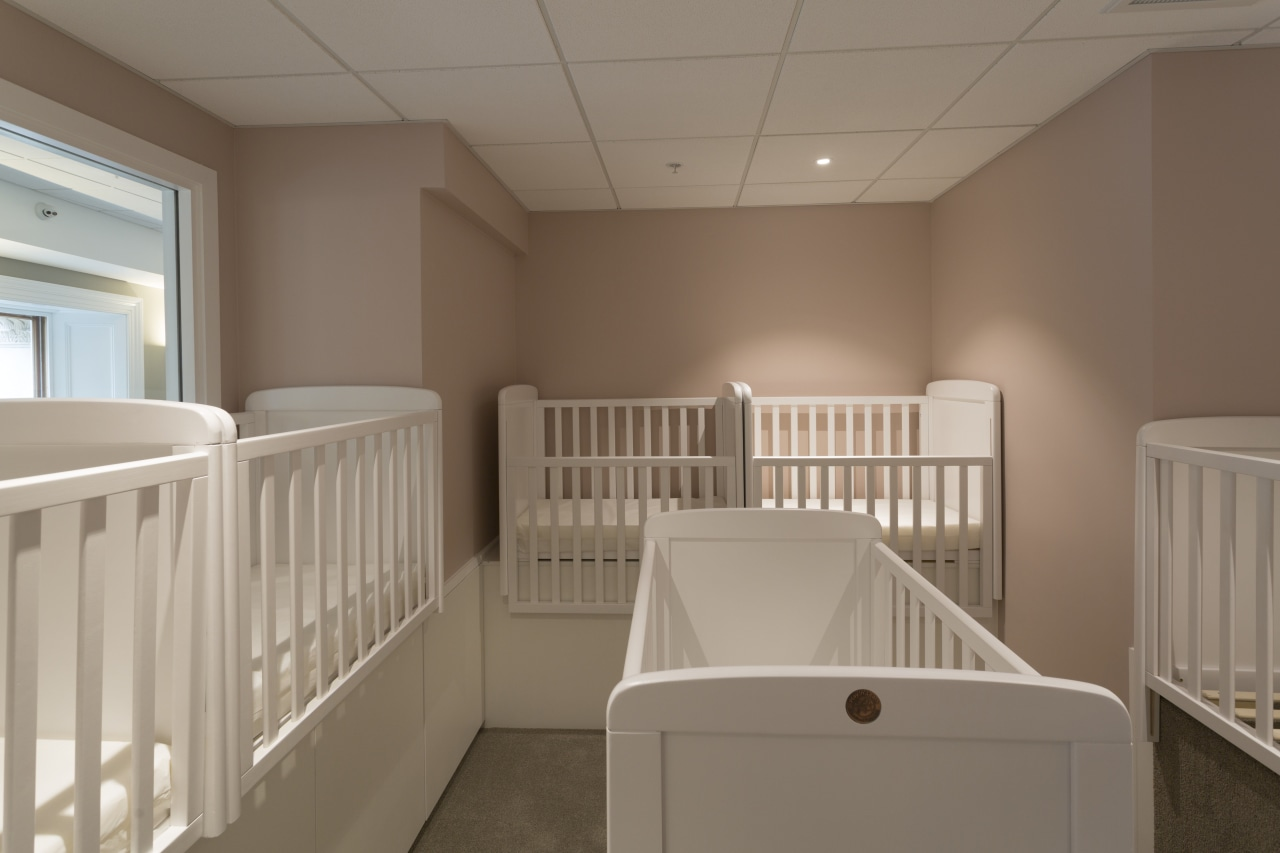 The sleeping room for infants enrolled at Cosmokids ceiling, floor, furniture, home, product, room, window, brown, gray