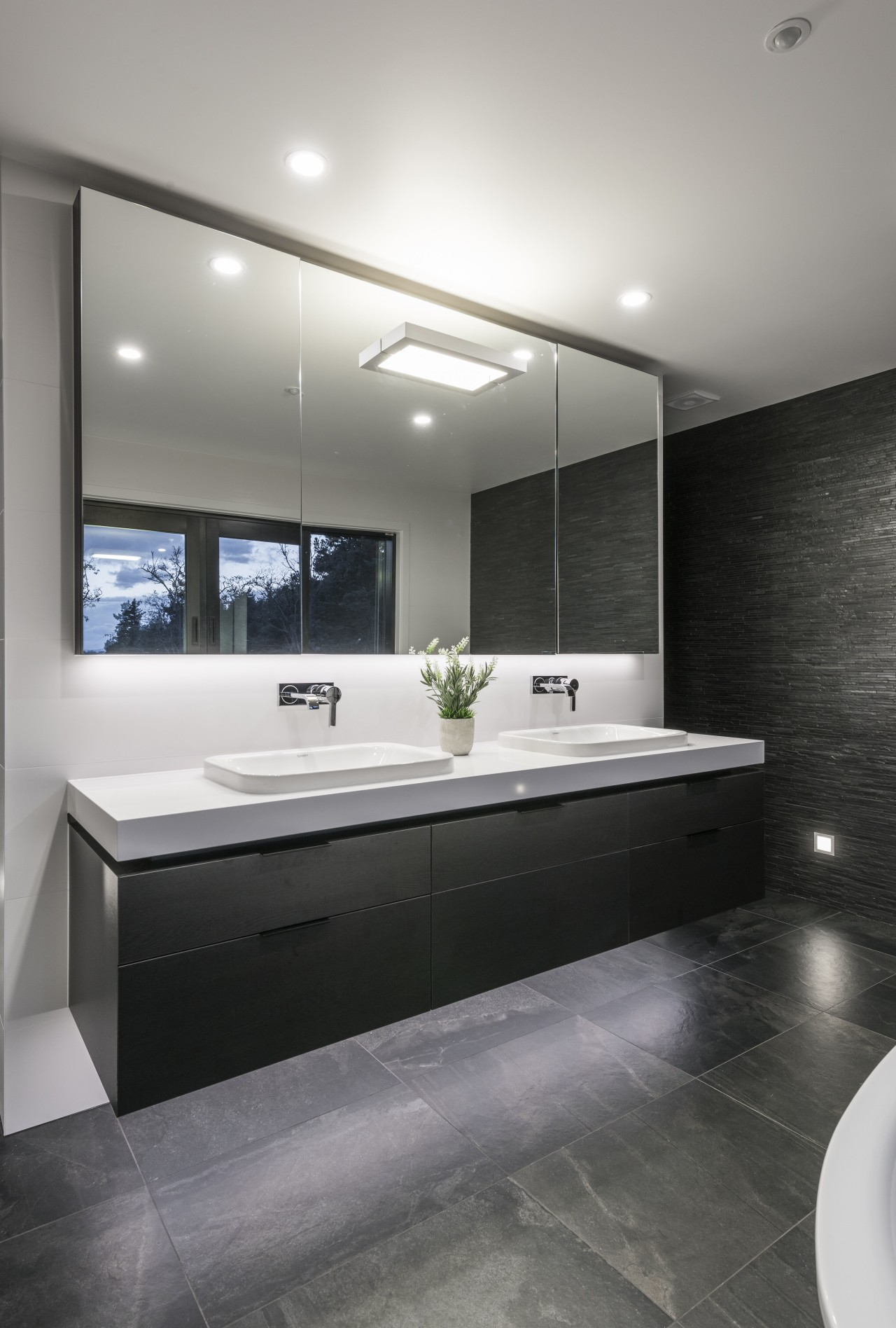 Under-vanity lighting highlights the stone-look flooring in this architecture, bathroom, ceiling, countertop, floor, interior design, product design, room, sink, gray, black