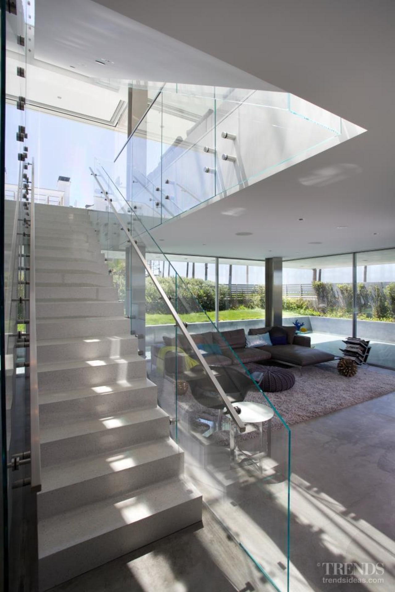 The first floor of this beachhouse accommodates a apartment, architecture, condominium, daylighting, glass, handrail, house, interior design, mixed use, real estate, stairs, structure, gray, white