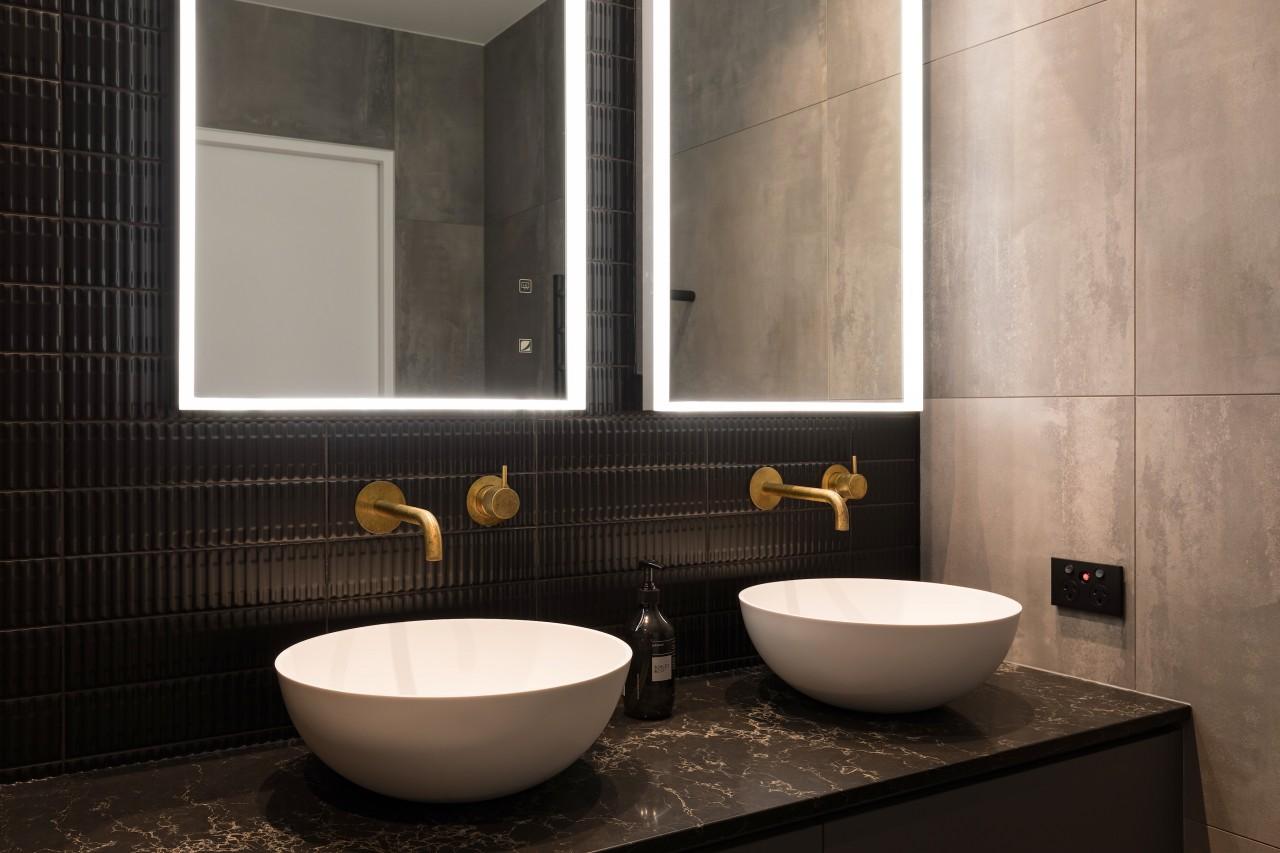 The illuminated mirror cabinets provide discreet storage along