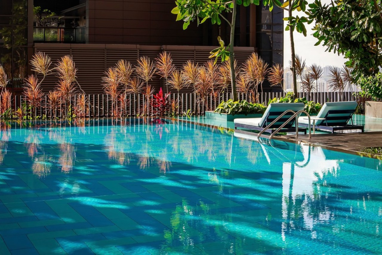 This open pool area is slice of paradise leisure, plant, property, reflection, resort, swimming pool, tree, water, water feature, teal