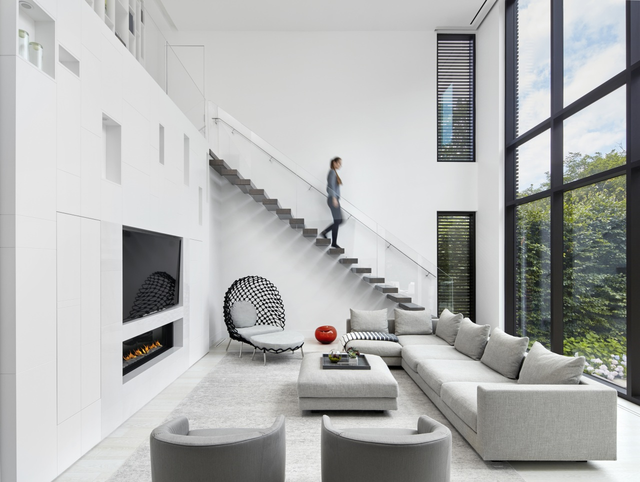 A contemporary cantilevered wood staircase, set behind a