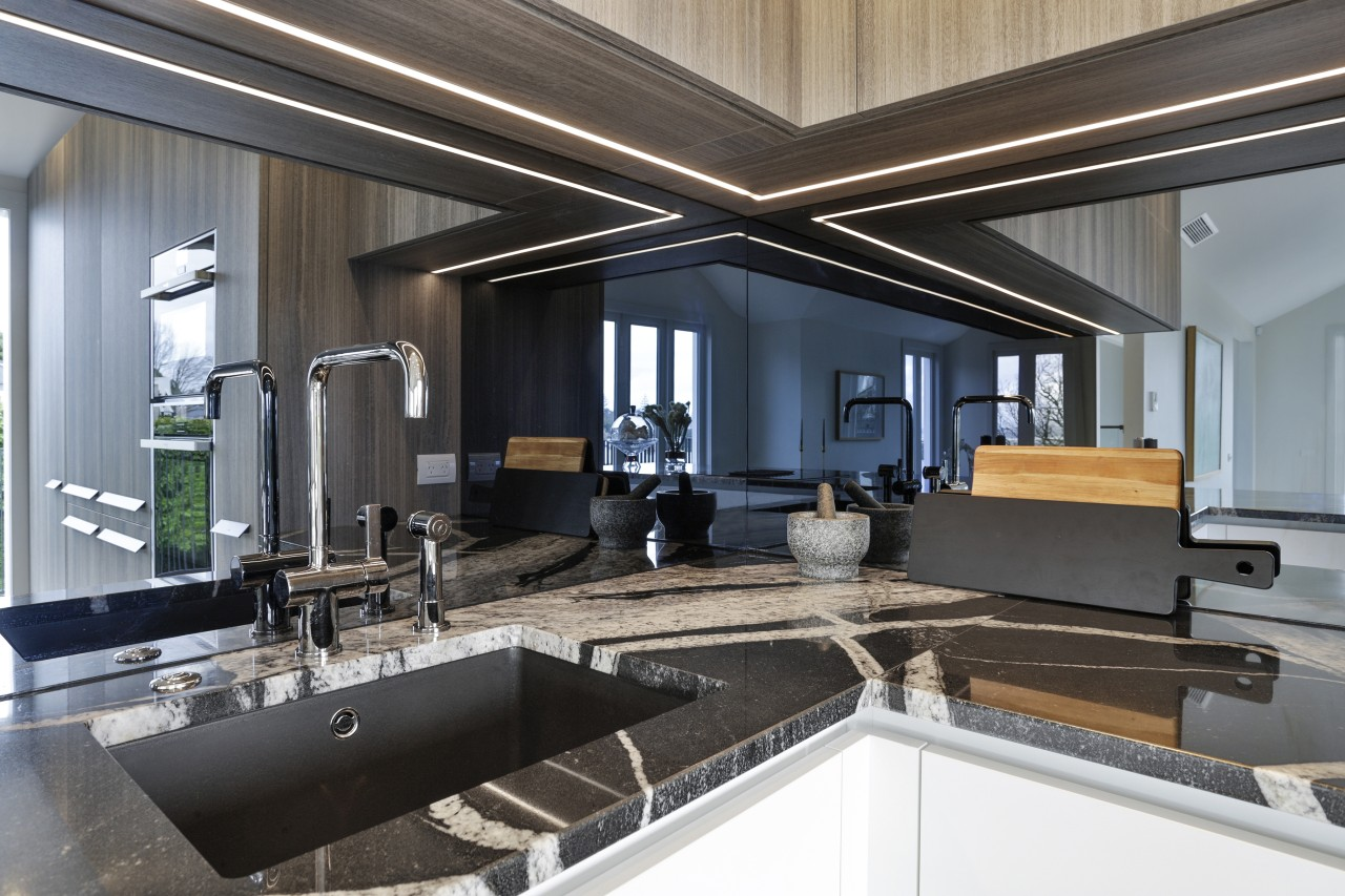 A smokey mirror splashback adds to the kitchen's
